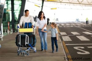 Family walking outside airport terminal with luggage